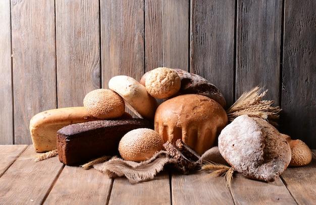Pane diverso nel cesto di vimini sul tavolo su fondo di legno