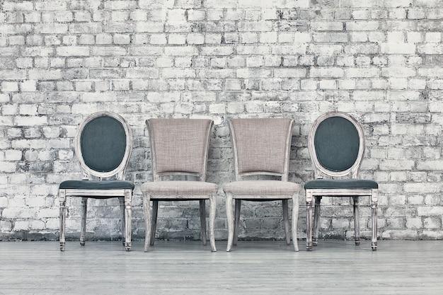Diverse sedie in fila contro un muro di mattoni bianchi