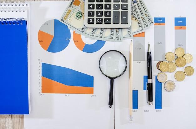 Diversi grafici grafici con dollari e una calcolatrice sulla scrivania dell'ufficio analisi finanziaria