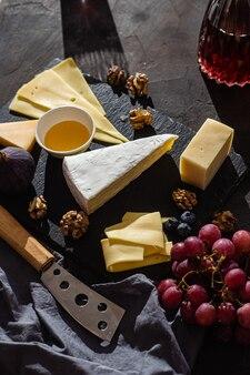 Diversi formaggi su un piatto con miele