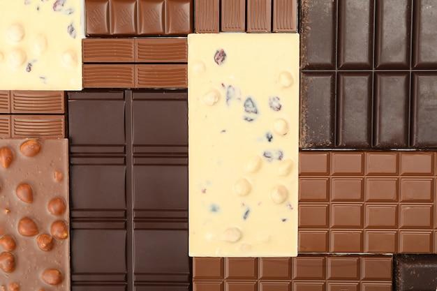 Diverse barrette di cioccolato su tutto lo sfondo. vista dall'alto