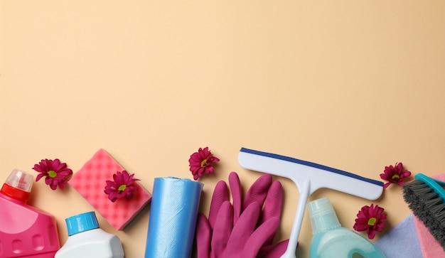 Diversi strumenti di pulizia su sfondo beige, spazio per il testo