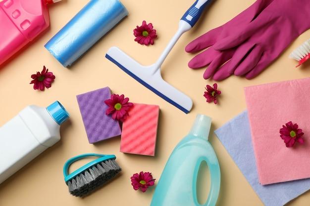 Diversi strumenti di pulizia su sfondo beige, vista dall'alto