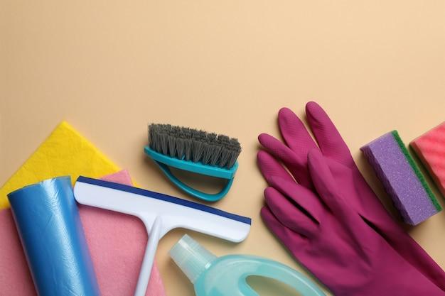 Diversi strumenti di pulizia su beige, spazio per il testo