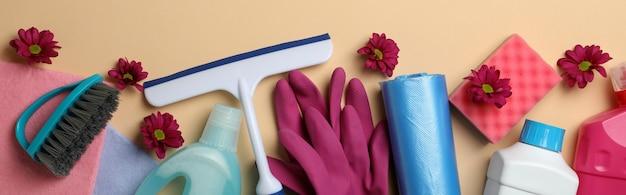 Diversi strumenti di pulizia su beige, vista dall'alto