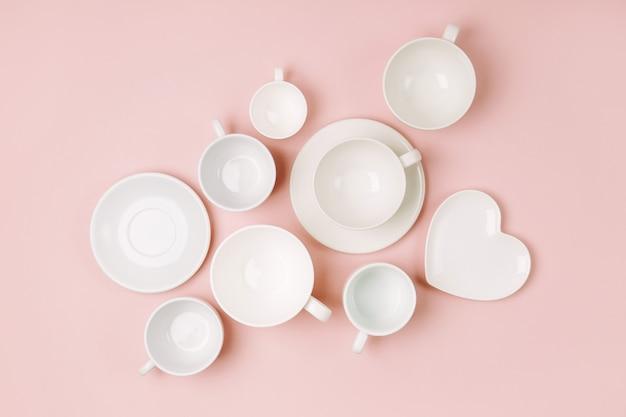 Diverse tazze di caffè su sfondo rosa pallido