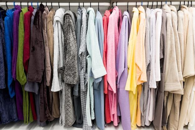 Accappatoi di colore diverso sull'appendiabiti nel bagno con doccia, in negozio o al mercato.