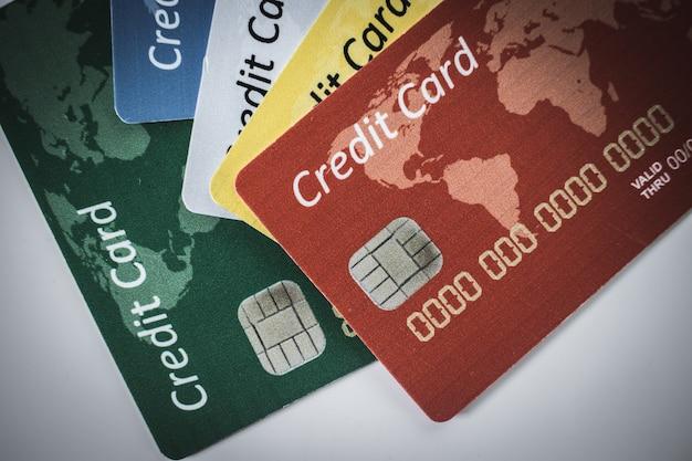Carta di credito scheggiata di colore diverso sdraiata su sfondo bianco