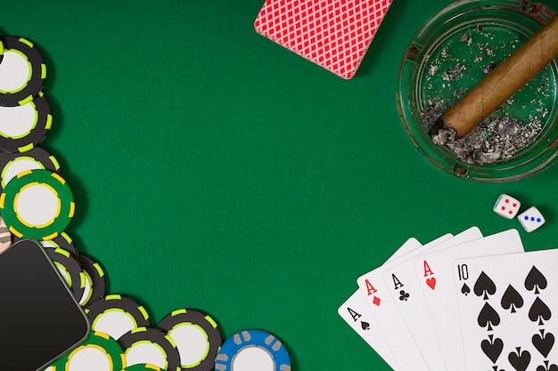 Chip di colore diverso per giochi d'azzardo e carte da gioco su sfondo verde. vista dall'alto. natura morta. copia spazio