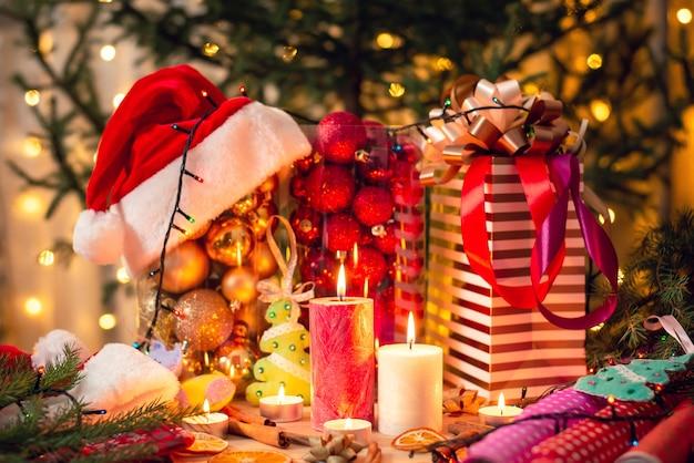 Diverse decorazioni natalizie colorate sul tavolo con candele accese nel mezzo