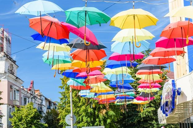 Diversi ombrelli colorati appesi sulla strada contro il cielo blu
