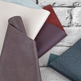 Campioni di texture in pelle naturale di diversi colori su sfondo grigio mattone