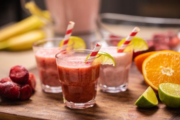Diversi colori di frullati rossi e rosa in tazze con cannucce di carta su un tavolo da cucina.