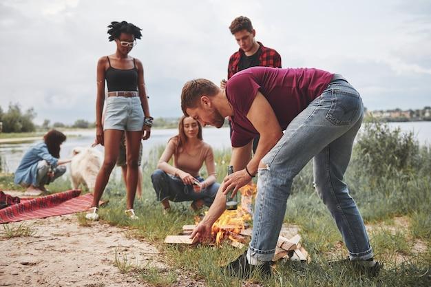 Culture diverse, un posto. un gruppo di persone fa un picnic sulla spiaggia. gli amici si divertono durante il fine settimana.