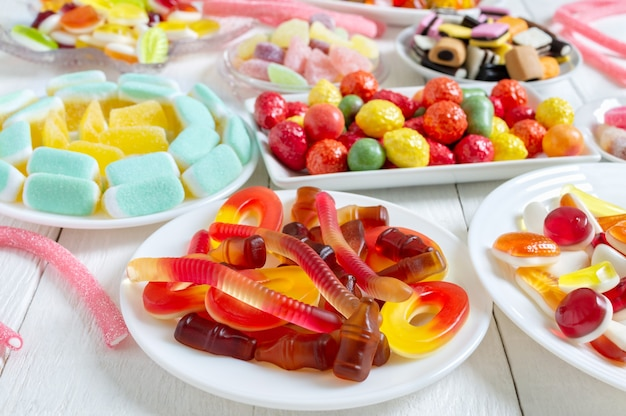 Diverse deliziose caramelle gommose colorate su piatti vista verticale