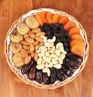 Diversi tipi di frutta secca su sfondo di legno