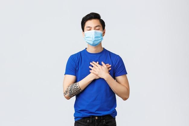 Emozioni diverse, distanza sociale, auto-quarantena sul coronavirus e concetto di stile di vita. sognante e premuroso, tenero uomo asiatico in maschera medica, chiudi gli occhi e tocca il cuore, prova amore e calore