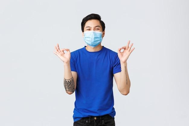 Emozioni diverse, distanza sociale, auto-quarantena su covid-19 e concetto di stile di vita. felice uomo asiatico felice in maschera medica, mostra il segno giusto, approva e mi piace l'idea, consiglia il prodotto