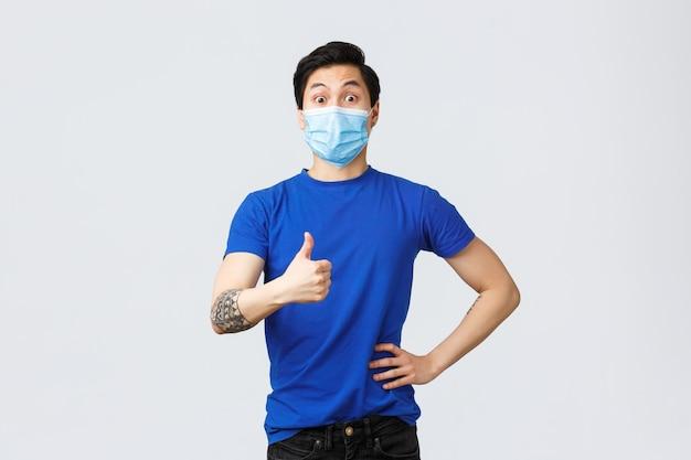 Emozioni diverse, distanza sociale, auto-quarantena su covid-19 e concetto di stile di vita. ragazzo asiatico di supporto sorpreso e impressionato pollice in su per una buona idea, indossando una maschera medica