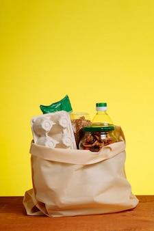 Alimento diverso in sacco di carta sulla tavola di legno, su fondo giallo