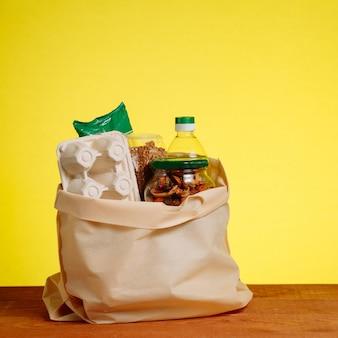 Cibo diverso nel sacchetto di carta sul tavolo di legno, su sfondo giallo