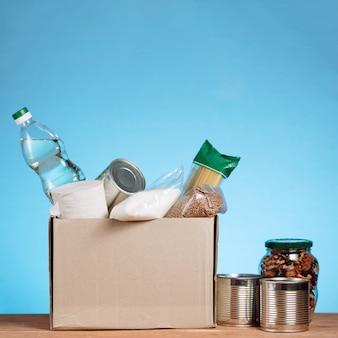 Cibo diverso in una scatola di volontari. donate box, donazione e concetto di beneficenza. casella di donazione con cibo su sfondo blu. immagine quadrata