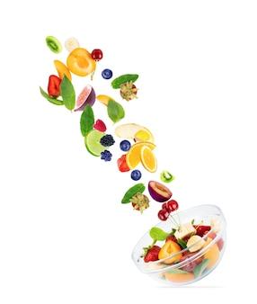 Frutti diversi, in volo volano in un piatto con frutta, su sfondo bianco