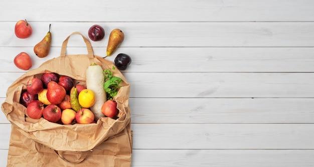 Diversi tipi di frutta e verdura in un sacchetto di carta su una superficie di legno