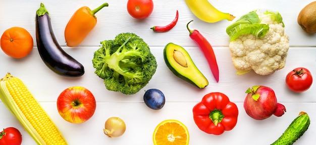 Frutta e verdura differenti sulla tavola di legno bianca sulla cucina. sfondo di cibo sano. vista dall'alto, posizione piatta