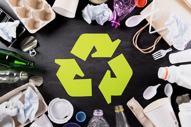Diversi materiali di immondizia con il riciclaggio del simbolo su sfondo nero. ricicli il concetto