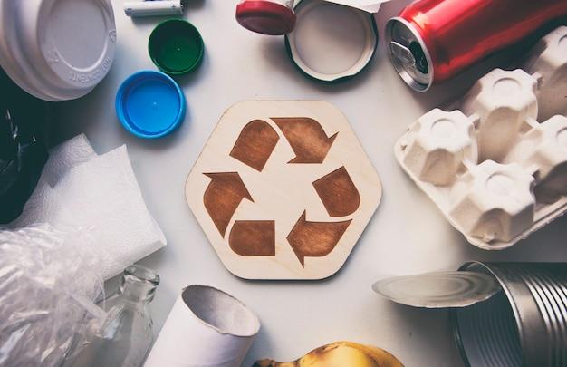 Immondizia diversa sul tavolo e icona di riciclaggio tra di loro