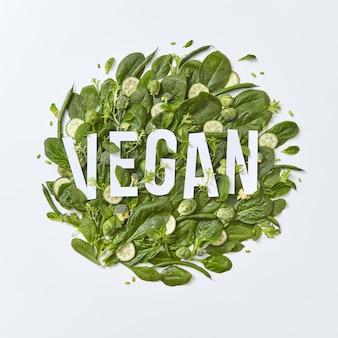 Diverse verdure verdi broccoli, spinaci, cavolini di bruxelles, asparagi, foglie di menta e fette di cetriolo su uno sfondo grigio con spazio per il testo. ingredienti per una sana insalata vegetariana flat lat
