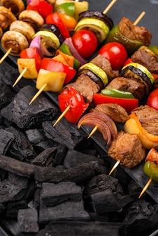 Diversi spiedini alla griglia con carne, funghi, salsicce e verdure su spiedini
