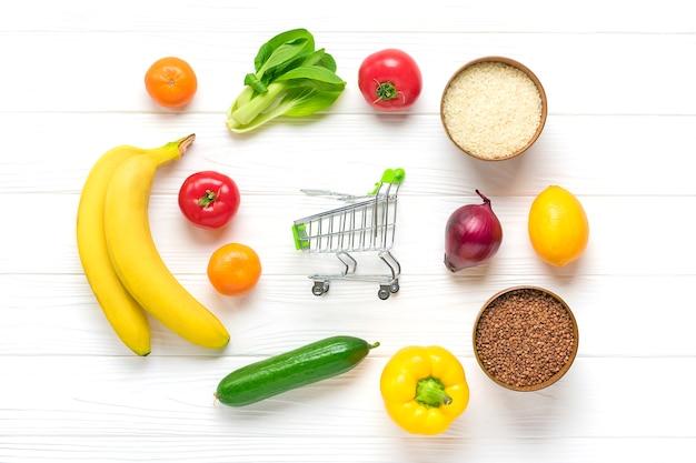 Diversi alimenti biologici - grano saraceno, riso, peperone giallo, pomodori, banane, lattuga, verde, cetriolo, cipolle, carrello della spesa