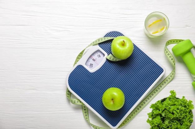 Cibo sano diverso con metro a nastro, bilancia e manubri su superficie di legno bianco. concetto di dieta
