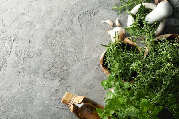 Diverse erbe, olio e mortaio su sfondo grigio, spazio per il testo
