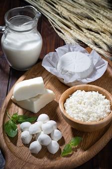 Ricotta casalinga differente con latte sulla tavola di legno.