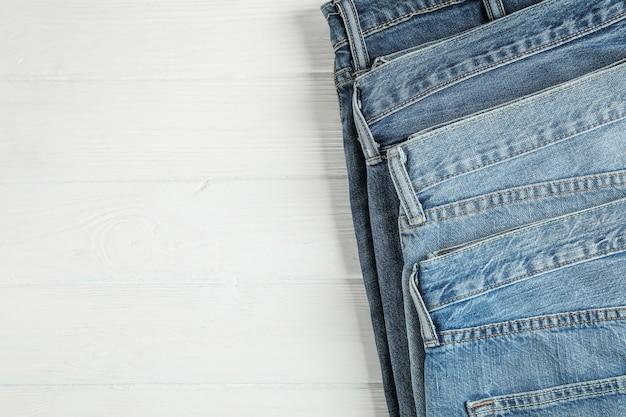 I jeans differenti hanno piegato su un fondo di legno bianco, spazio per testo