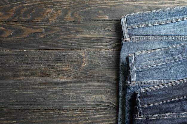 I jeans differenti hanno piegato su un fondo di legno, spazio per testo
