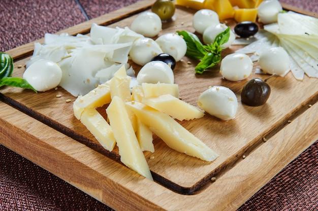 Diversi tipi di formaggio su fondo in legno