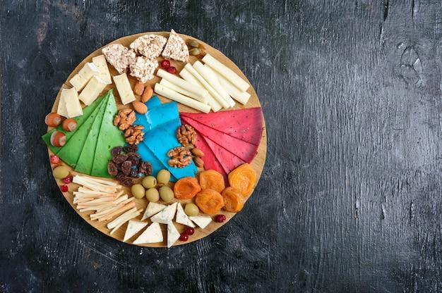 Diversi tipi di formaggi, albicocche secche, pane integrale, noci, olive, capperi su una tavola di legno. tagliere di formaggi, snack. vista dall'alto
