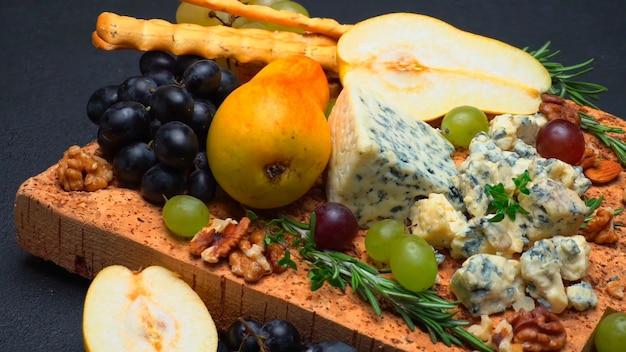 Diversi tipi di formaggi, frutta e snack su tavola di legno rustica