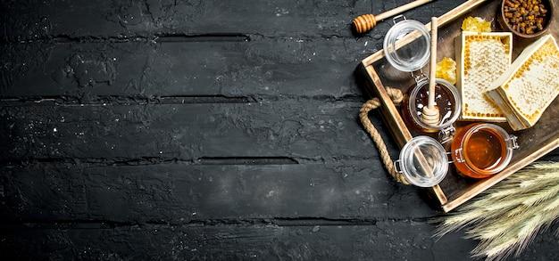 Diversi tipi di miele sul vassoio in legno. su un rustico nero.