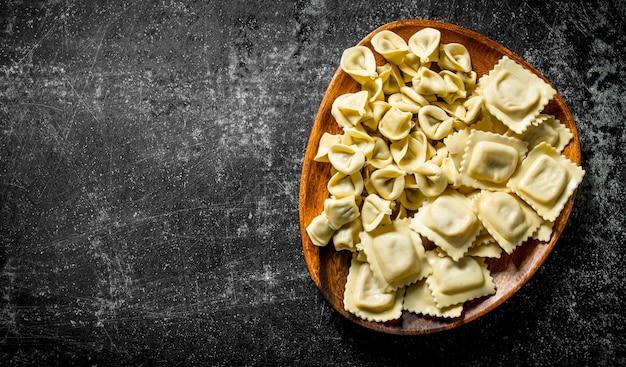 Diversi tipi di pasta cruda italiana con carne di manzo. su rustico scuro