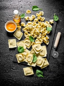 Diversi tipi di pasta cruda italiana con salsa e spinaci sul tavolo rustico