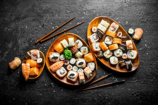 Diversi tipi di involtini di sushi giapponesi con salmone, gamberetti e verdure. sulla tavola rustica nera