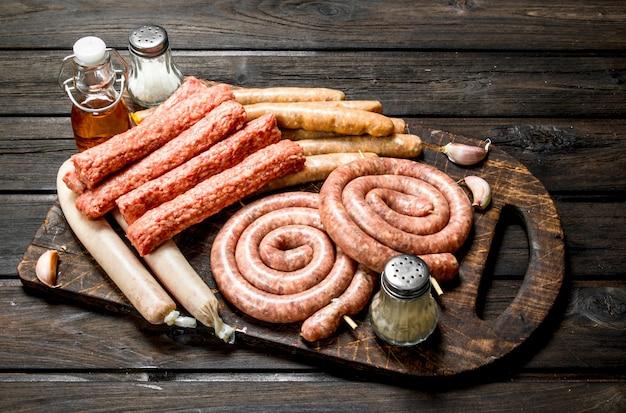 Diversi tipi di salsicce crude su tavola di legno con spezie. su una superficie di legno.