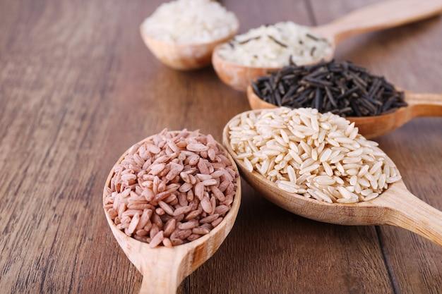 Diversi tipi di riso in cucchiai sul tavolo di legno