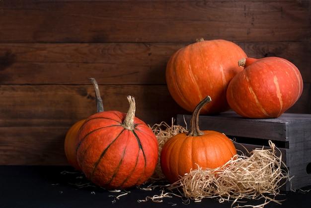 Diversi tipi di zucche arancioni mature su uno sfondo di legno con spazio di copia. raccolto autunnale prima di halloween.