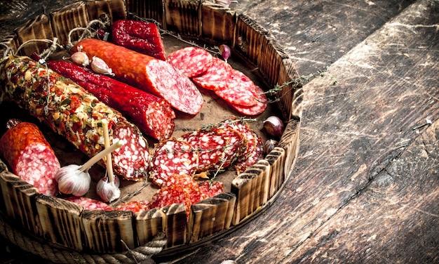 Diversi tipi di salame sulle tavole. su un tavolo di legno.